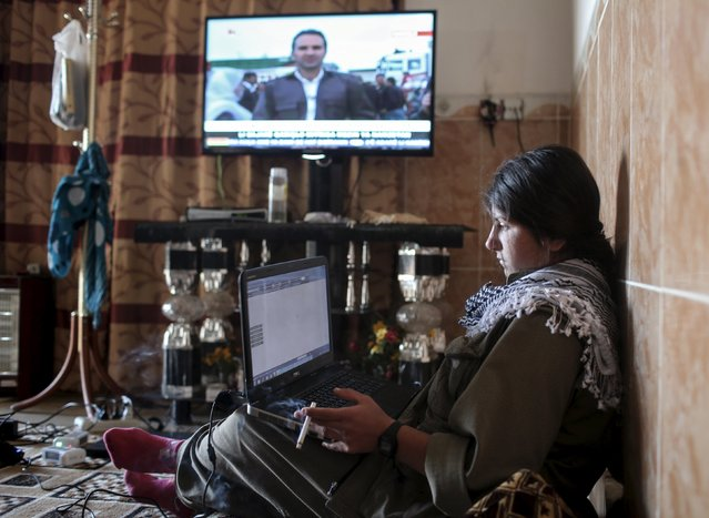 A female Kurdistan Workers Party (PKK) fighter works on her laptop while watching a Kurdish TV station at a base in the Sinjar mountains, March 11, 2015. (Photo by Asmaa Waguih/Reuters)