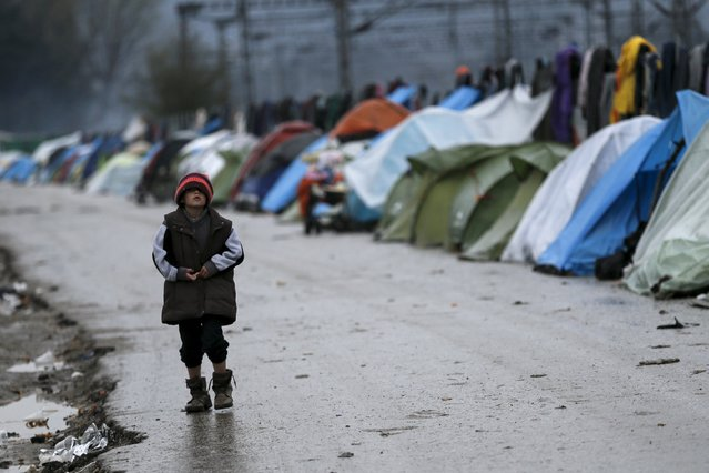 A boy makes his way next to tents at a makeshift camp for refugees and migrants at the Greek-Macedonian border, near the village of Idomeni, Greece March 16, 2016. (Photo by Alkis Konstantinidis/Reuters)