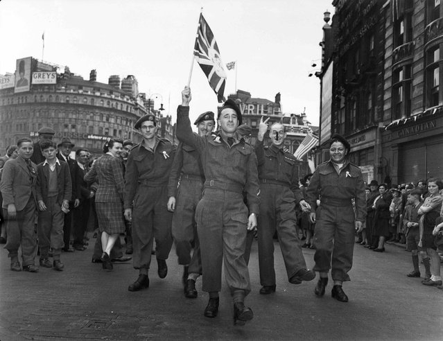 Canadian soldiers celebrate VE-Day at Piccadilly Circus, London, May 8,1945, in this handout photo provided by Library and Archives Canada. (Photo by Lieut. Arthur L. Cole/Reuters/Canada Department of National Defence/Library and Archives Canada)