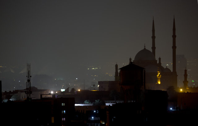 The great Mosque of Muhammad Ali Pasha in the Citadel and the great Pyramids, in rear left, are in darkness after having the main lighting switched off to mark Earth Hour, in Cairo, Egypt, Saturday, March 19, 2016. (Photo by Amr Nabil/AP Photo)
