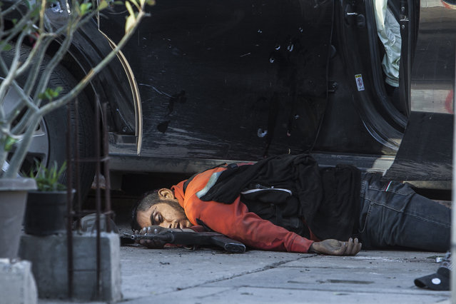 In this Tuesday, February 7, 2017 photo, a man lies dead over a weapon after a confrontation with the military in Culiacan, Mexico. The Sinaloa state prosecutor's office said in a statement that several suspects and a marine died in the early morning clash after heavily armed men attacked the marines while on patrol in the city. (Photo by Rashide Frias/AP Photo)
