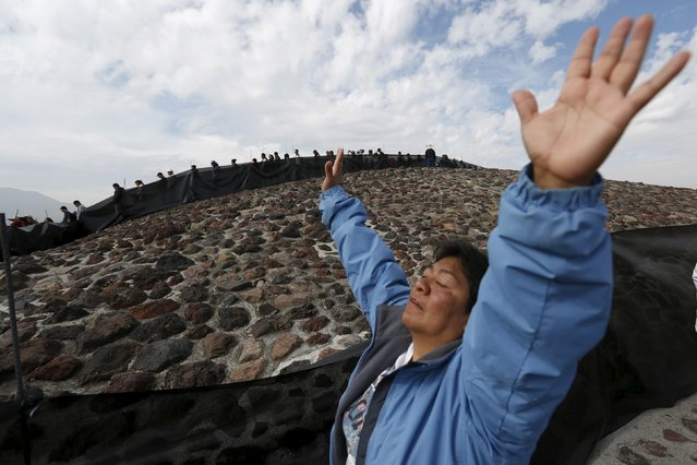 A woman raises her arms towards the sun to welcome the spring equinox while she is standing on the Pyramid of the Sun in the pre-hispanic city of Teotihuacan on the outskirts of Mexico City, Mexico, March 20, 2016. (Photo by Edgard Garrido/Reuters)