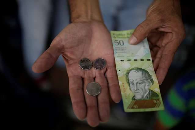 A vendor holds coins of 50 bolivar and a 50 bolivar note for a photo, in a street stall in downtown Caracas, Venezuela December 29, 2016. (Photo by Marco Bello/Reuters)