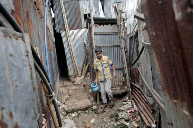 In this June 1, 2016, file photo, a Bangladeshi boy walks out of a toilet at a slum in Dhaka, Bangladesh. A new report by the United Nations children's agency on Friday, April 5, 2019, says the lives and futures of more than 19 million Bangladeshi children are at risk from colossal impacts of devastating floods, cyclones and other environmental disasters linked to climate change. (Photo by A.M. Ahad/AP Photo/File)