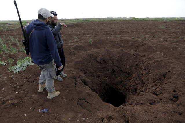 Rebel fighters from Jaysh al-Sunna inspect a hole in the ground after an unexploded shell fell in a farmland in Mkahaleh village, in the southern countryside of Aleppo, Syria March 14, 2016. (Photo by Khalil Ashawi/Reuters)