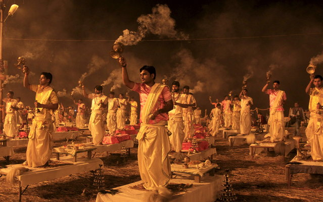 "Hindu priests hold traditional incense lamps as they perform a ritual known as ""Aarti"" on the banks of Sangam – the confluence of the Ganges, Yamuna and mythical Saraswati rivers – during the annual religious festival of Magh Mela in Allahabad, India, February 14, 2016. The festival is an annual religious event held during the Hindu month of Magh, when thousands of devotees take a holy dip at Sangam. (Photo by Jitendra Prakash/Reuters)"
