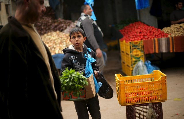 Palestinian boy Mohammad al-Bana, 10, sells mints at a market in Gaza City March 29, 2016. Bana, whose father is unemployed, earns around 10 Shekels ($2.5) per day. The boy starts working after finishing school. He hopes to continue education and become an engineer in the future. (Photo by Mohammed Salem/Reuters)