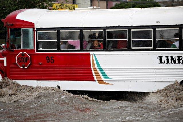 A boy gestures from inside a bus moving through a flooded street during heavy rains in Ciudad Juarez, Mexico May 12, 2015. (Photo by Jose Luis Gonzalez/Reuters)
