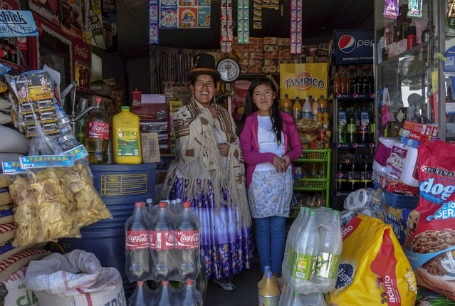 Lucia Mayta, 43, and her daughter Luz Cecilia, 12, pose for a photograph inside their bodega in La Paz February 24, 2014. Lucia studied until the fourth grade of primary school, and knows how to read and write and do basic math. Lucia runs a bodega, and the family live in a back room. She hopes to build a house in the future. Luz Cecilia is in seventh grade and wants to be a singer. (Photo by David Mercado/Reuters)