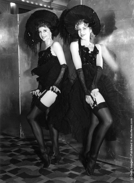 Two Can-Can dancers adjusting the suspenders on their stockings