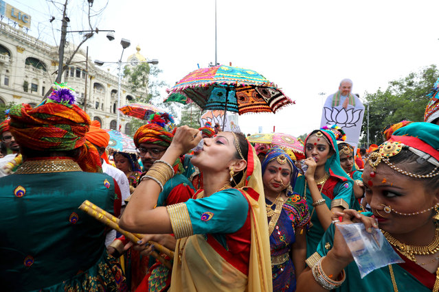 Bharatiya Janata Party (BJP) activists and dancers drink water as they walk a mass rally for BJP President Amit Shah in Kolkata, Eastern India, 14 May 2019. The parliamentary elections, which began on 11 April 2019, are to be conducted in seven phases throughout India and the result will be announced on 23 May. (Photo by Piyal Adhikary/EPA/EFE)