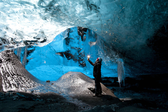 Rob Lott stands under the crystal ice cave in the Vatnajokull Glacier, Iceland. (Photo by Rob Lott/Barcroft Media)