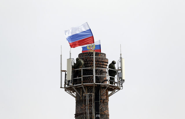 Armed men, believed to be Russian servicemen, stand guard at the top of a chimney located near the naval headquarters, with Russian flags installed nearby, in Sevastopol, March 19, 2014. Around a dozen Ukrainian servicemen, unarmed and in civilian clothes, walked out of the Ukrainian naval headquarters in the Crimean port of Sevastopol on Wednesday after it was taken over by pro-Russian forces, a Reuters witness said. (Photo by Vasily Fedosenko/Reuters)