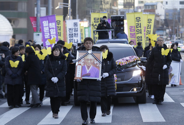 A mourner with a portrait of the deceased Kim Bok-dong, a former South Korean s*x slave, marches toward the Japanese Embassy during her funeral ceremony in Seoul, South Korea, Friday, February 1, 2019. Hundreds of mourners gathered Friday near the embassy for the funeral of Kim forced as a girl into a brothel and sexually enslaved by the Japanese military in WWII. (Photo by Ahn Young-joon/AP Photo)