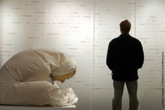 A man views a wall listing the known names of 800 out of an estimated 10,000 victims of Nazi experiments as a a memorial entitled Man with Sheet created by Australian artist Ron Mueck crouches silently as a testiment to the medical professions shame at the Medical History Museum