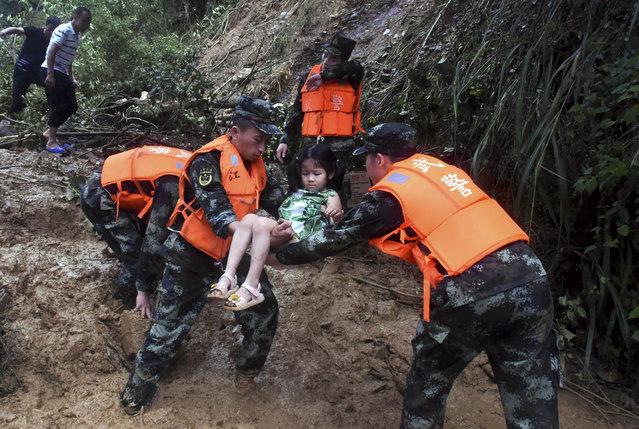 Armed police transfer a girl at Shanxi Village of Yongxin County in Ji'an City, east China's Jiangxi Province, June 8, 2019. China's national observatory on Sunday renewed a yellow alert for rainstorms in some southern areas. From Sunday morning to Monday morning, heavy rain to rainstorms are expected to hit parts of Zhejiang, Fujian, Jiangxi, Hunan, Guizhou, Guangdong provinces and Guangxi Zhuang Autonomous Region, the National Meteorological Center said. (Photo by Peng Zhaozhi/Xinhua News Agency)