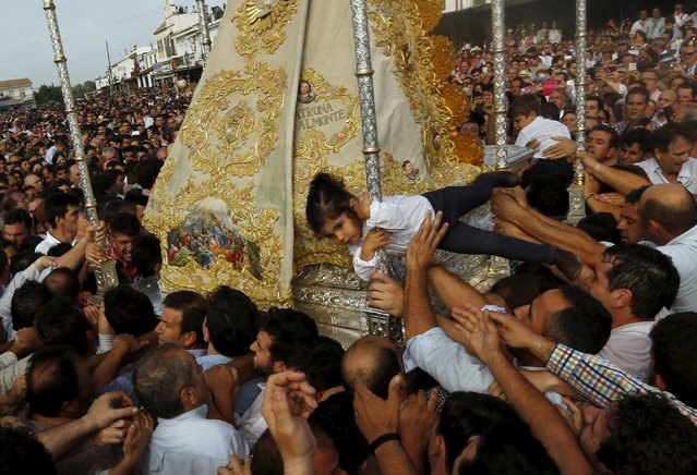 Pilgrims carry a girl to touch the Virgin of El Rocio during a procession around the shrine of El Rocio in Almonte, southern Spain, May 25, 2015. (Photo by Marcelo del Pozo/Reuters)