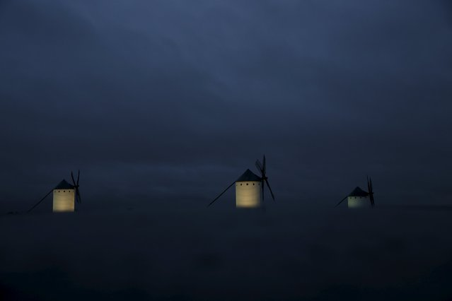 Windmills are seen at dusk in Campo de Criptana, Spain, April 4, 2016. Locals believe that Miguel de Cervantes drew inspiration from the windmills of Campo de Criptana to narrate the battle between Don Quixote and the windmills he mistook for giants. (Photo by Susana Vera/Reuters)