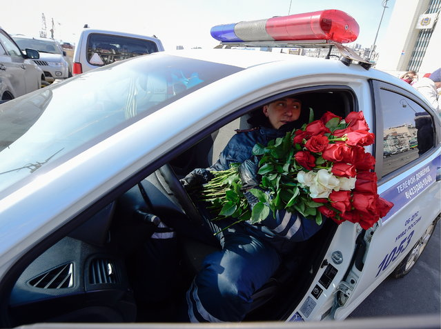 A traffic policeman gives flowers to female drivers ahead of International Women's Day in Vladivostok, Russia on March 7, 2017. (Photo by Yuri Smityuk/TASS via Getty Images)