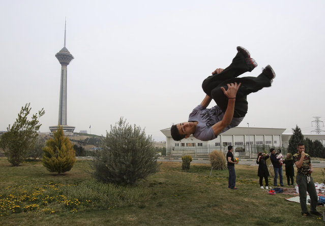 """Iranian Omid Khosravi practices parkour during the ancient festival of Sizdeh Bedar, an annual public picnic day on the 13th day of the Iranian new year, in Tehran, Iran, Wednesday, April 2, 2014. Sizdeh Bedar, which comes from the Farsi words for """"thirteen"""" and """"day out"""", is a legacy from Iran's pre-Islamic past that hard-liners in the Islamic Republic never managed to erase from calendars. Many say it's bad luck to stay indoors for the holiday. (Photo by Vahid Salemi/AP Photo)"""