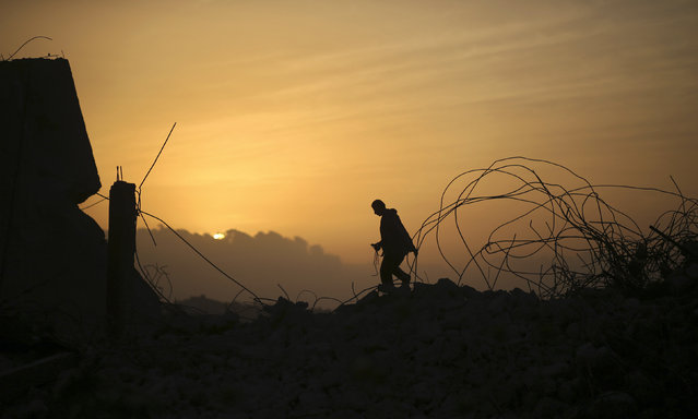 A Palestinian man walks atop a destroyed building during sunset in the northern Gaza Strip April 7, 2014. (Photo by Mohammed Salem/Reuters)