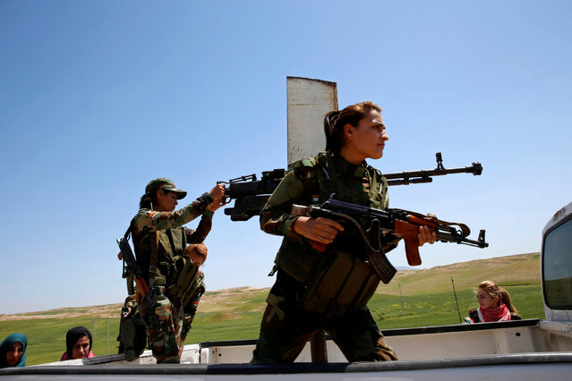 Yazidi female fighter Asema Dahir (L), 21, holds a weapon as she rides a pickup truck during a deployment near the frontline of the fight against Islamic State militants in Nawaran near Mosul, Iraq, April 20, 2016. (Photo by Ahmed Jadallah/Reuters)