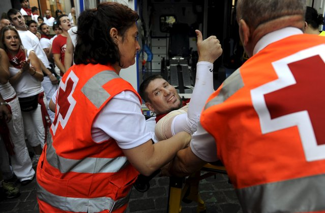 An unidentified runner gestures while being attended by medical services following the first running of the bulls of the San Fermin festival in Pamplona, northern Spain, July 7, 2015. (Photo by Eloy Alonso/Reuters)
