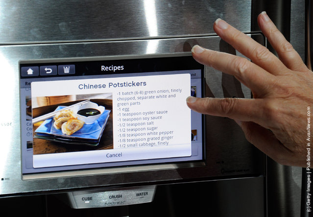 An attendee uses an interface on a refrigerator using LG's newest Smart ThinQ technology at the LG Electronics booth at the 2012 International Consumer Electronics Show
