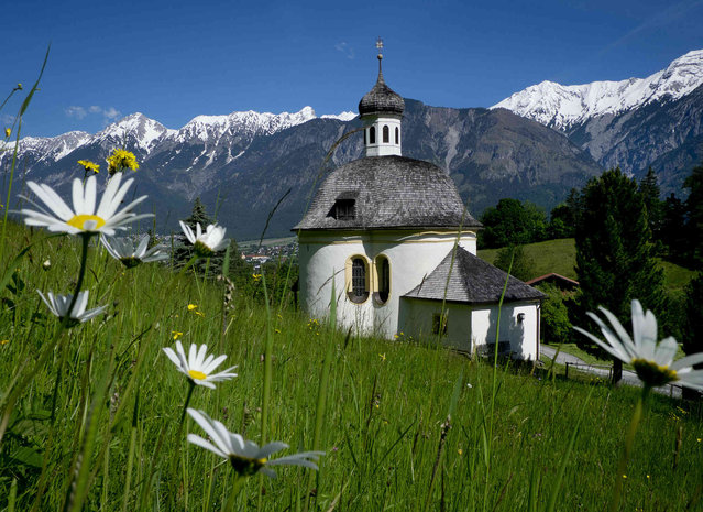 A small chapel stands on a hill in front of the North Chain mountains in Innsbruck, Austria, Saturday, June 1, 2019. Snow persists on the peaks while lower slopes sport summer flowers with lush green fields. (Photo by Michael Probst/AP Photo)
