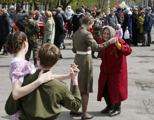 People dance during a ceremony to congratulate veterans of World War Two with Victory Day in the centre of Russia's Siberian city of Krasnoyarsk, May 7, 2014. Russia marks the anniversary of their victory over Nazi Germany on May 9. (Photo by Ilya Naymushin/Reuters)