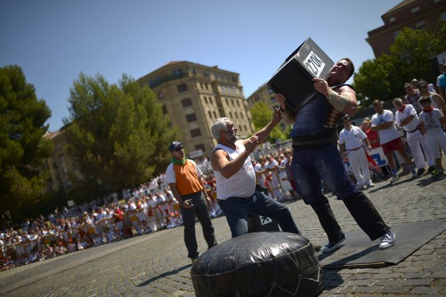 "Basque stone lifter (Harrijasotzaile) Inaxio Perurena raises a 270 kg (595 lbs.) granite block during an exhibition of traditional rural sports on the seventh day of the San Fermin festival in Pamplona, northern Spain, July 12, 2015. The festival, a heady mix of drinking, dancing, late nights and bullfights, made famous by Ernest Hemingway in his novel ""The Sun Also Rises"", runs for nine days until July 14. (Photo by Vincent West/Reuters)"