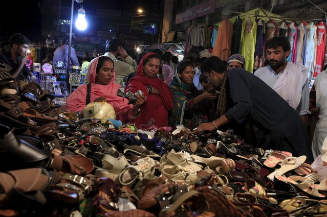Women buy shoes at a stall ahead of Eid al-Fitr celebrations, which marks the end of Ramadan, in Rawalpindi, Pakistan, July 13, 2015. (Photo by Faisal Mahmood/Reuters)