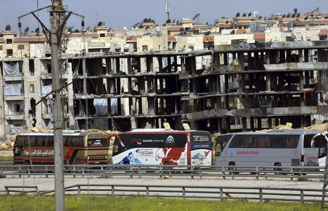 In this photo released by the Syrian official news agency SANA, buses carry Syrian citizens who evacuated from the two pro-government villages of Foua and Kfarya, pass in front of damaged buildings upon their arrival at a handover point between the two rebels and the Syrian forces on the outskirts of Aleppo city, Syria, Friday, April, 21, 2017. (Photo by SANA via AP Photo)