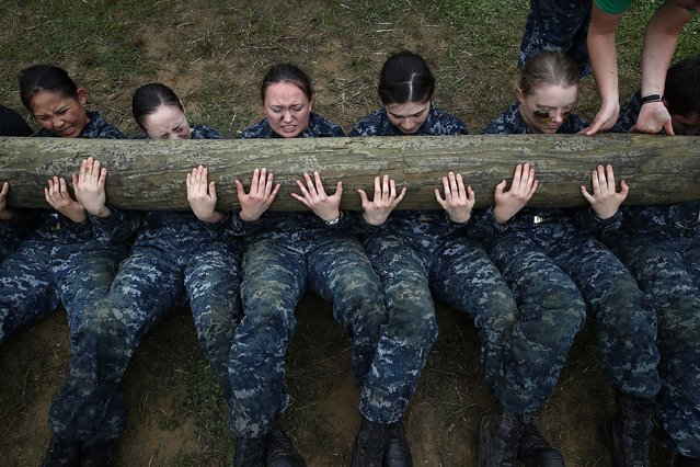 Female Naval Academy plebes perform push ups with a twelve foot log on top of them during the annual Sea Trials May 17, 2016 at the Naval Academy in Annapolis, Maryland. The Naval Academy freshman class endures 14 hours of rigorous physical and mental challenges during the annual Sea Trials training exercise as part of the culmination of their freshman year at the academy. (Photo by Win McNamee/Getty Images)