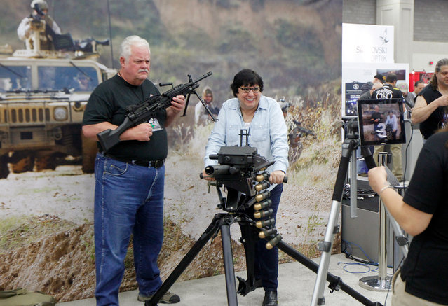 Gun enthusiasts poses for a picture with an FN MK 48 machine gun and a MK 19 grenade launcher at the National Rifle Association's annual meetings & exhibits show in Louisville, Kentucky, May 21, 2016. (Photo by John Sommers II/Reuters)