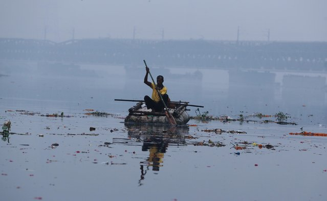 A man paddles a home-made boat across Yamuna river on a smoggy afternoon in the old quarters of Delhi, India, October 30, 2019. (Photo by Adnan Abidi/Reuters)