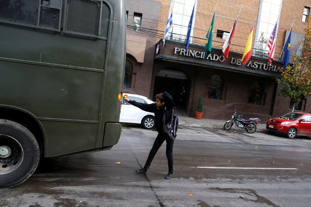 A demonstrator uses a spray on a riot police vehicle during an unauthorized march called by secondary students to protest against government education reforms in Santiago, Chile, May 26, 2016. (Photo by Ivan Alvarado/Reuters)