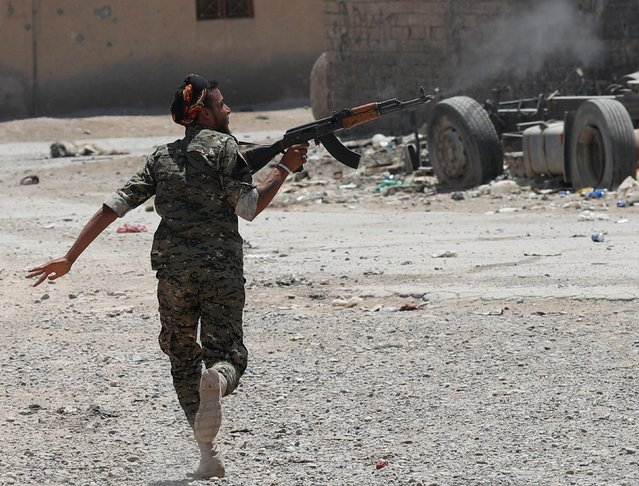 A Kurdish fighter from the People's Protection Units (YPG) fires his rifle at Islamic State militants as he runs across a street in Raqqa, Syria, July 2017. (Photo by Goran Tomasevic/Reuters)