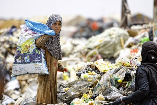 An Iraqi girl searches through garbage for recyclable items on June 10, 2014, at a waste dump on the outskirts of the shrine city of Najaf, in central Iraq. (Photo by Haidar Hamdani/AFP Photo)