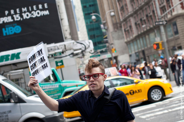 A man holds up a sign advertising comedy shows to people in Times Square on March 23, 2012 in New York City