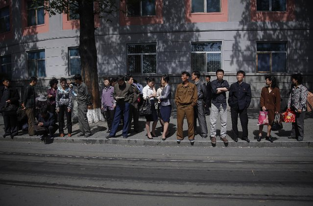 North Koreans wait in line for a city trolley, Monday, May 4, 2015 in Pyongyang, North Korea. The city trolley is one of the more common modes of public transportation used by commuters to get around the city. (Photo by Wong Maye-E/AP Photo)