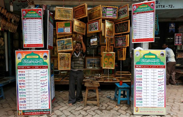A salesman hangs religious pictures for sale ahead of the Muslim fasting month of Ramadan in Kolkata, India, June 6, 2016. (Photo by Rupak De Chowdhuri/Reuters)