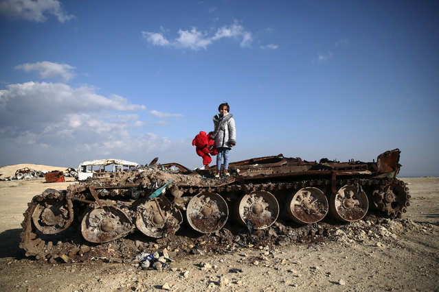 11-year-old Syrian girl Rawan poses on a destroyed tank with her stuffed bear near the village of Yazi Bagh, about six kilometres from the Bab al-Salamah border crossing between Syria and Turkey in the north of Aleppo province, on February 19, 2019. (Photo by Nazeer Al-Khatib/AFP Photo)