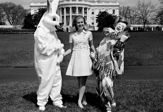 Tricia Nixon walks the White House grounds March 27, 1970 with a couple of Springtime friends – circus clown Bobby Kay and the Easter Bunny, a White House staffer who prefers to remain anonymous. (Photo by Henry Burroughs/AP Photo)