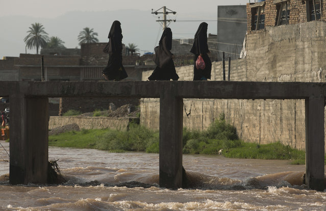 Pakistani women cross a stream flooded due to heavy rains in Rawalpindi, Pakistan, Wednesday, July 22, 2015. Pakistan's military deployed helicopters and boats Wednesday to evacuate flood victims from the country's north, where monsoon rains and flash floods washed away several villages this week. (Photo by Mohammad Sajjad/AP Photo)