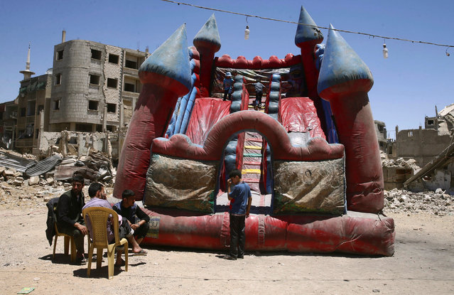 Children play inside an inflatable castle during Eid al-Fitr celebration in the rebel-held besieged Douma neighbourhood of Damascus, Syria June 26, 2017. (Photo by Bassam Khabieh/Reuters)