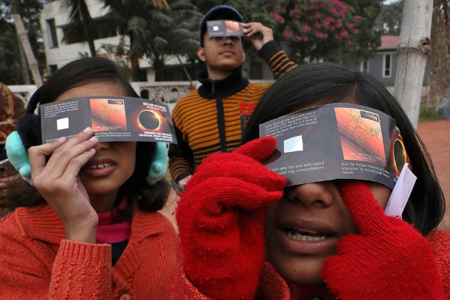 Children use solar viewers to watch the solar eclipse in Kolkata, India, December 26, 2019. (Photo by Rupak De Chowdhuri/Reuters)