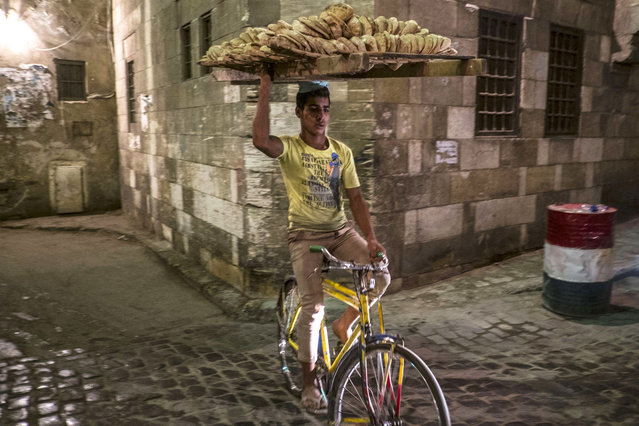 An Egyptian bread seller rides his bicycle as Muslim worshipers break the day-long fast during the holy month of Ramadan in Cairo Khan el-Khalili district on July 8, 2014. During the holy month of Ramadan, Muslims are supposed to go without food, drink, smoking and s*x and to refrain from impure thoughts from sunrise to sunset. (Photo by Khaled Desouki/AFP Photo)