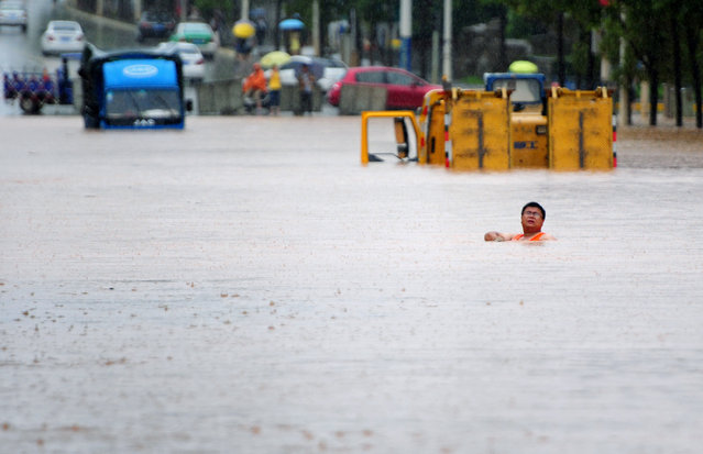 A worker tries to make his way through a flooded area in Jiujiang, Jiangxi Province, China, June 19, 2016. (Photo by Reuters/China Daily)
