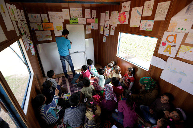 A volunteer teacher teaches inside a mobile educational caravan for children who do not have access to schools on the outskirts of the Syrian rebel-held town of Saraqib, Idlib province March 10, 2016. (Photo by Khalil Ashawi/Reuters)